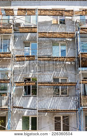 Block Of Flats Facade Fragment With Scaffolding In Sunlight