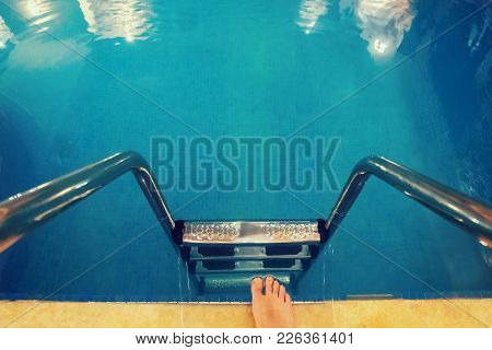 A Person Takes A Step Towards The Water In The Home Swimming Pool. Legs With At The Blue Swimming Po