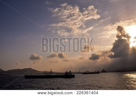 Silhouette Of An Offshore Drilling Rig And Supply Vessel At Sunset