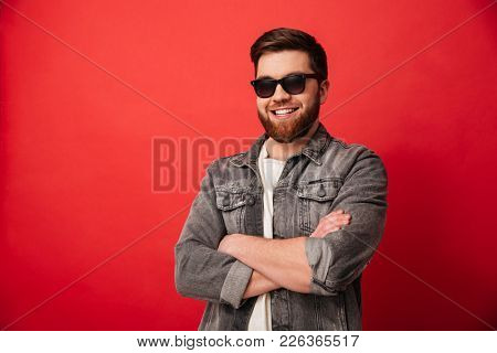 Portrait of attractive man 30s in sunglasses smiling on camera and posing with hands folded isolated over red background