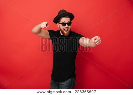 Image of unshaved young man wearing black sunglasses and hat smiling and pointing fingers on camera meaning hey you isolated over red wall