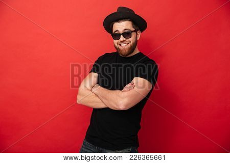 Portrait of irresistible stylish man 30s in hat and sunglasses smiling on camera and posing with hands crossed isolated over red background