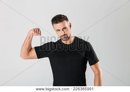 Portrait of a confident mature sportsman showing biceps isolated over gray background