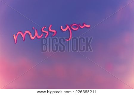 Handwritten phrase miss you on the pink and purple blur background, enjoying relationships, affection and first love concept, happy Valentines day holiday