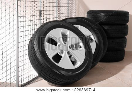 Car tires with rims in automobile service center