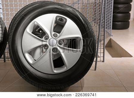 Car tire with rim indoors