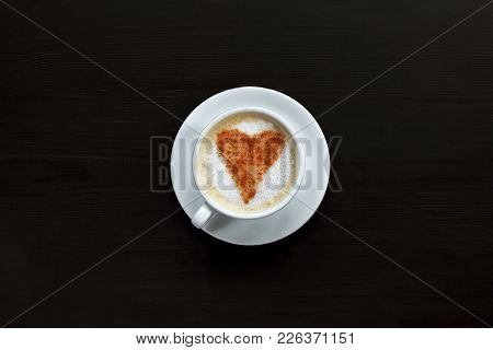 Cup Of Frothy Cappuccino Decorated With Heart Of Cinnamon Stands On Dark Table Top View / Hot Love W