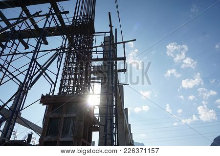 Silhouette Photograph Of Concrete Structure During Construction On Blue Sky Background