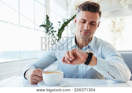 Image of brunette man having stubble sitting alone in city cafe with cup of cappuccino looking on wrist watch and waiting for meeting