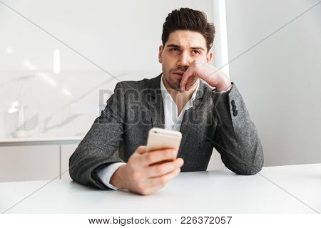 Photo of tired displeased young businessman indoors looking aside using mobile phone.