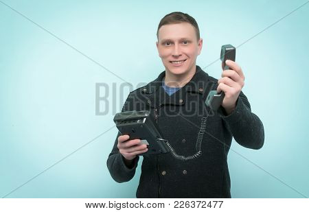 Cheerful Man Is Holding In His Hands A Phone And Stretches A Handset Ahead Isolated On Blue Backgrou