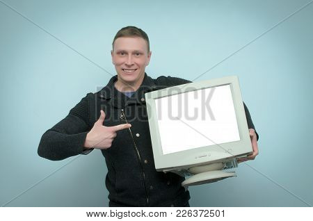 Happy Cheerful Man Is Holding In Hands A Old Computer Monitor With Blank Screen And Is Showing On It