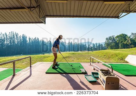 Young Woman Practices Her Golf Swing On Driving Range, View From Behind,young Girls Practicing Drivi