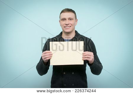 Cheerful Young Man Is Holding In Hands An Empty Wooden Board With Copy Space. Billboard.