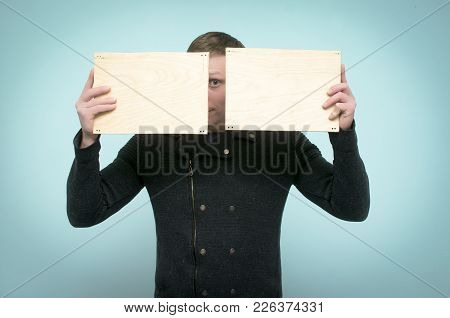 Cheerful Young Man Is Hiding His Face Behind A Two Empty Wooden Boards With Copy Space In His Hands.