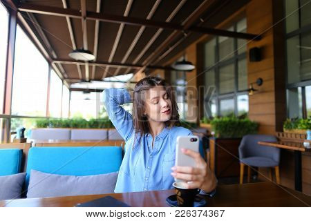 Pretty Girl Making Selfie By Smartphone At Cafe With Cup Of Coffee  . Young Lady Dressed In Blue Shi