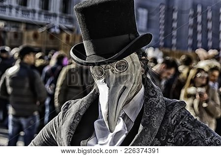 Portrait Of A Woman Wearing Mask Of A Plague Doctor During The Venetian Carnival Party In San Marco