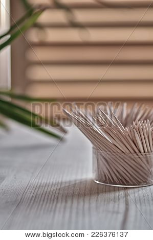 Wooden Toothpicks Stand On Wooden Table. On Background Of Window And Green Twig Tropical Plant. Side