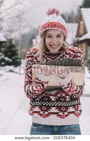 Girl carrying firewood for heat in the winter. Woman with log of firewood.