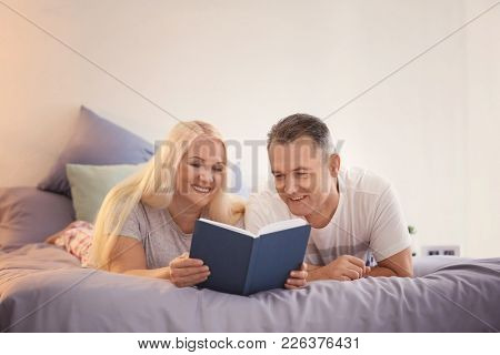 Senior couple reading book on bed together