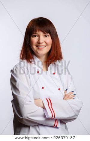 Photo of female chef in white robe on empty background