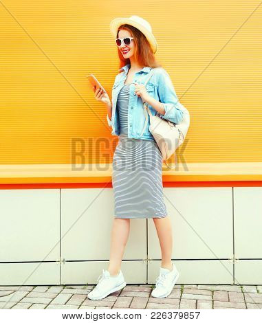 Fashion Cool Girl Is Using The Smartphone Walking In The City On Orange Background