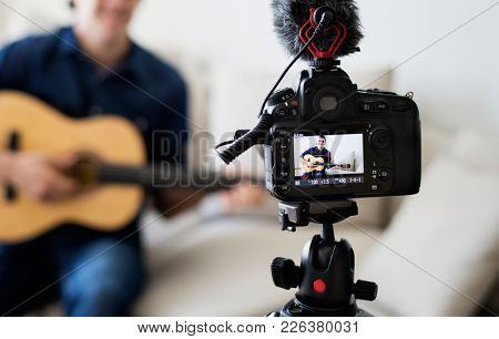 Male vlogger recording music related broadcast at home
