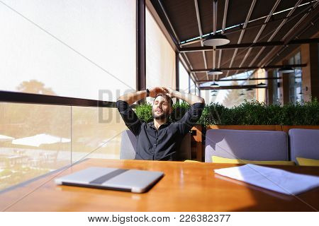 European Translator Sorting Papers And Closing Laptop Lid At Cafe. Young Persistent Man Dressed In B