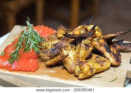 Pile Of Roasted Grilled Chicken Wings On Oak Wooden Board.