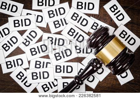 One Gavel Like Those Used On Auctioning With The Word Bid On Wooden Background.