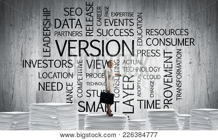 Business Woman In Suit Standing On Pile Of Documents With Business-related Terms On Background. Mixe