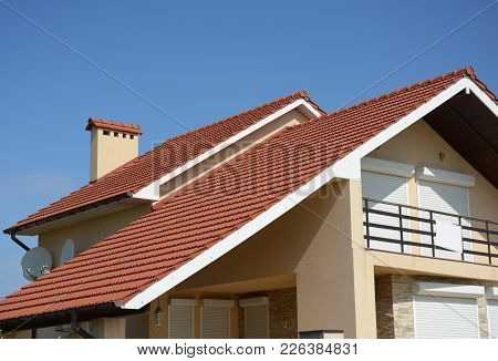 Cozy House With Balcony, Clay Tiled Roof And Gable And Valley Type Of Roof Construction. Building At