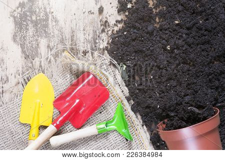Overturned Flower Pot And Gardening Tools - Flower Pot Full Of Soil Overturned On A Wooden Workplace