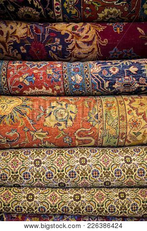 Close up of many Persian carpets placed on top of each other.