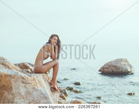 Sad Woman Outdoors Thinking On Rocky Beach. Slim Girl Lonely And Sadness On The Beach With The Sea I