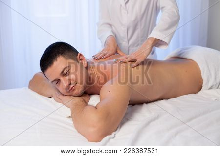 Male Masseur Makes Therapeutic Massage In The Spa 1