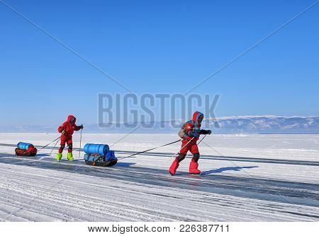 Lake Baikal, Irkutsk Region, Russia - March 08, 2017: Two Women On Skates Actively Move On Ice