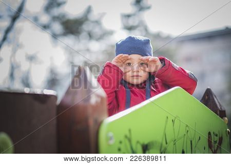 Adorable Toddler Boy Playing On A Fort In The Park