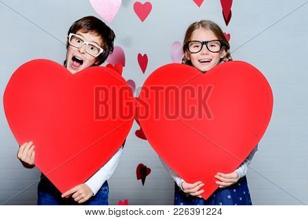 Happy pre-teen boy and girl holding two red hearts. Friendship. First love. Valentine's Day.
