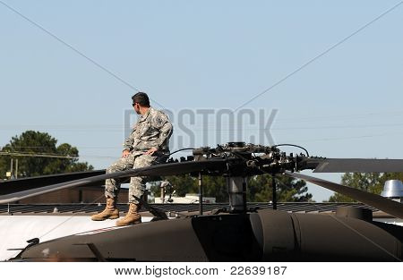 Pilot Resting On Top Of Helicopter