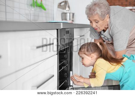 Cute little girl and her grandmother making cookies on kitchen
