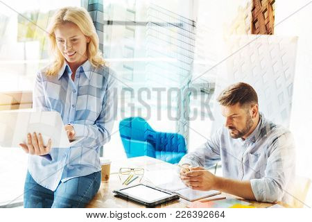 Useful Gadgets. Calm Busy Serious Man Sitting At The Table With A Smartphone In His Hand While A Che