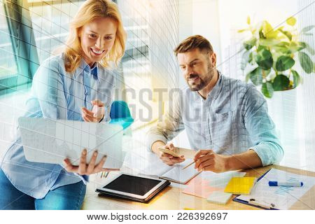 Amazing. Cheerful Clever Young Woman Sitting On The Table With A Laptop In Her Hands And Pointing To