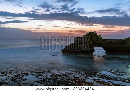 Sunset Near Famous Tourist Landmark Of Bali Island - Tanah Lot & Batu Bolong Temple. Long Exposure E