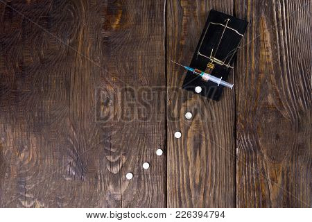 Syringe trapped in a mousetrap. Concept of drug addiction. Copy paste. poster