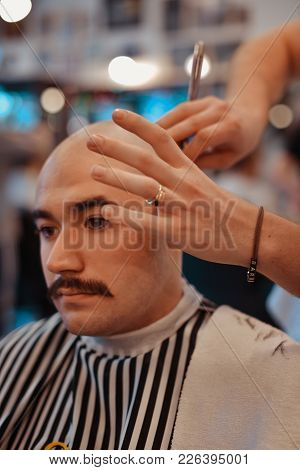 The Man Is Shaving Everything Apart From The Mustache. Shaving A Head In A Barbershop.