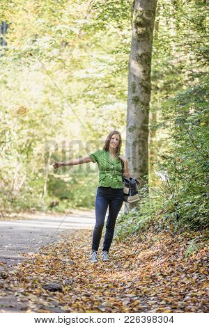 Young Woman Hitchhiker Standing On The Side Of The Road In Autumn Forest, Thumbing For Picking Her U