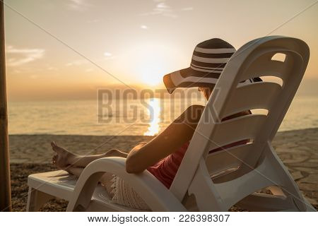 Woman In A Large Floppy Sunhat Relaxing On A Recliner At The Beach At Sunset Facing Out Over A Tranq