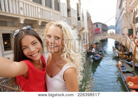 Tourists taking selfie at Venice canal, Europe summer travel holiday. Two multiracial girl friends having fun on vacation. Best friends women lifestyle.