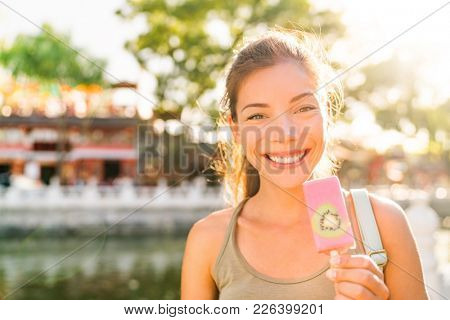 Asian tourist woman eating ice cream pop stick in Beijing city, China. Asia summer travel vacation. Healthy foodie girl eating frozen fruit snack near Houhai lake. Popular tourism destination.